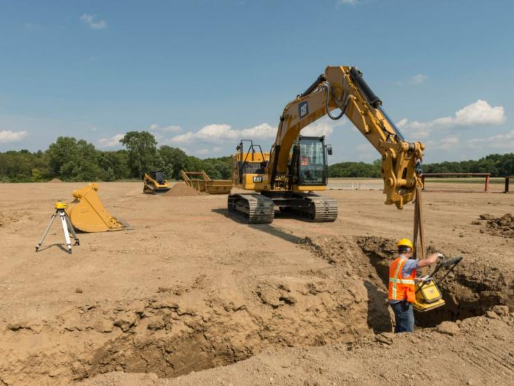 320 GC Excavator helping compact a trench